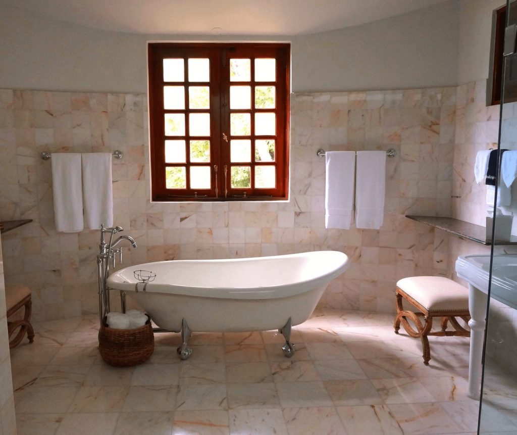 gorgeous traditional footed tub next to a country styled window