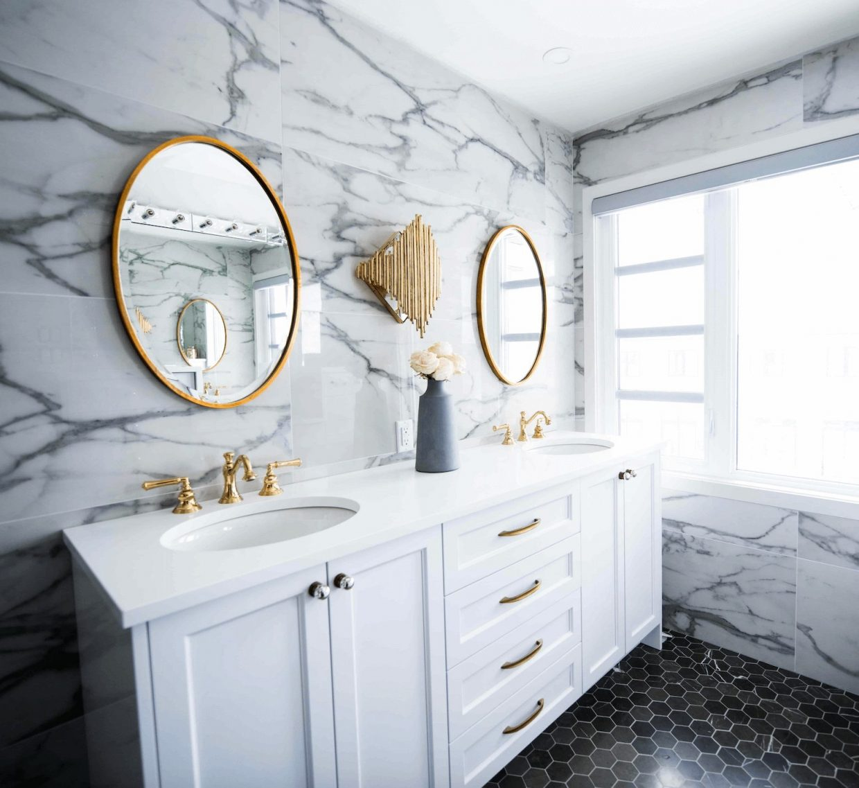 marble wall with gorgeous golden accents and a white vanity