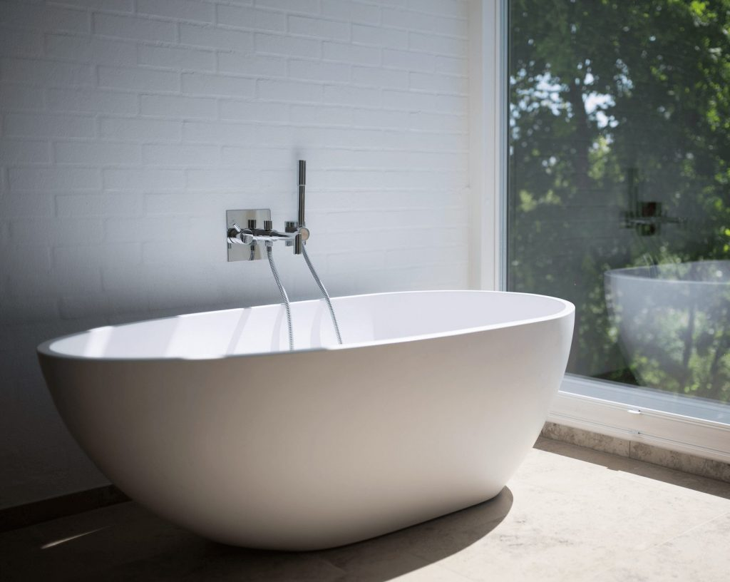 standalone bath tub next to large window